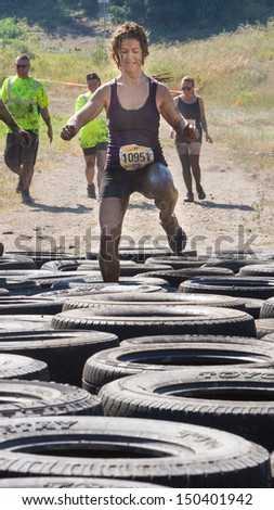 BOISE, IDAHO/USA - AUGUST 10: Runner 10951 does high knees to get past the tire obstacle at the The Dirty Dash in Boise, Idaho on August 10, 2013  - stock photo