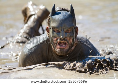 BOISE, IDAHO/USA - AUGUST 10: Runner dressed as batman swims in the mud during the The Dirty Dash in Boise, Idaho on August 10, 2013  - stock photo