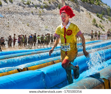 BOISE, IDAHO/USA - AUGUST 10, 2013: Runner 38174 sprints as Ronald Mcdonald at the The Dirty Dash - stock photo