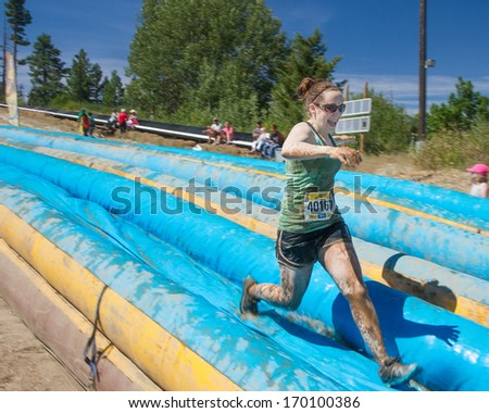 BOISE, IDAHO/USA - AUGUST 10, 2013: Runner 40167 sprints down the slide at the The Dirty Dash - stock photo