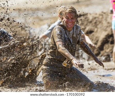 BOISE, IDAHO/USA - AUGUST 10, 2013: Runner 7358 tries to get away from someone making a big splash at the The Dirty Dash - stock photo
