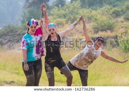BOISE, IDAHO/USA - AUGUST 10:teammates hold hands and cheer at the The Dirty Dash in Boise, Idaho on August 10, 2013  - stock photo