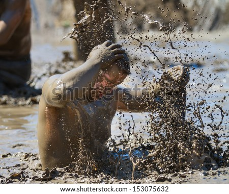 BOISE, IDAHO/USA - AUGUST 10: Unidentified man makes a splash with mud during the The Dirty Dash in Boise, Idaho on August 10, 2013  - stock photo