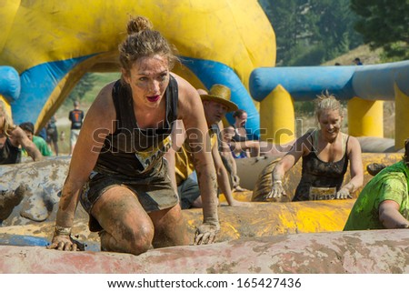 BOISE, IDAHO/USA - AUGUST 10: Unidentified runner on her knees as she climbs over an obstacle at the The Dirty Dash in Boise, Idaho on August 10, 2013 - stock photo
