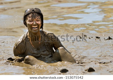 BOISE, IDAHO/USA - AUGUST 11:Unidentified woman stuck in the pit sitting on her bum at the The Dirty Dash in Boise, Idaho on August 11, 2013  - stock photo