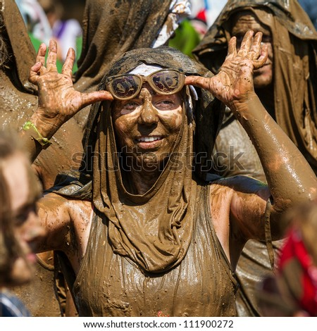 BOISE, IDAHO/USA - AUGUST 25 :Unidentified woman takes off her goggles after running in the Dirty Dash. the Dirty dash is a 10k run through obstacles and mud on August 25, 2012 in Boise, Idaho - stock photo