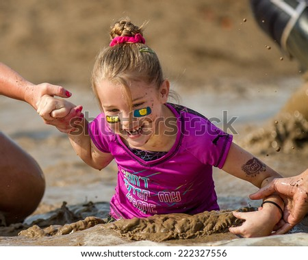 BOISE, IDAHO/USA - AUGUST 8, 2014: Unidentified young kid being helped through the mud pit at the Dirty Dash in Boise, Idaho - stock photo