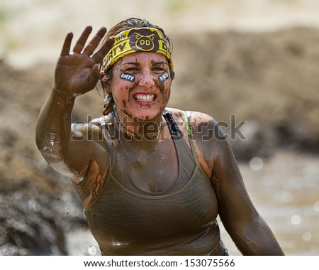 BOISE, IDAHO/USA - AUGUST 11: Woman coverd in mud waves at the camera wearing her dirty dash gear. Event took place at the The Dirty Dash in Boise, Idaho on August 11, 2013  - stock photo