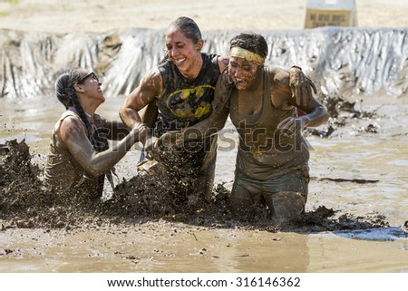 BOISE, IDAHO/USA - AUGUST 11, 2013: Women working together at the Dirty Dash in Boise, Idaho - stock photo