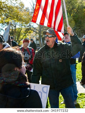 BOISE, IDAHO/USA - NOVEMBER 21, 2015: Protester holding the american flag protesting against accepting refugees into Boise, Idaho - stock photo