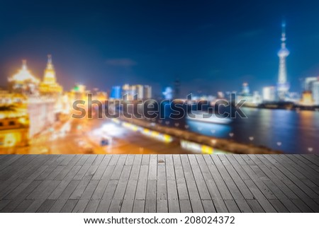 bokeh background city of beautiful shanghai at night with wooden floor as a prospect  - stock photo