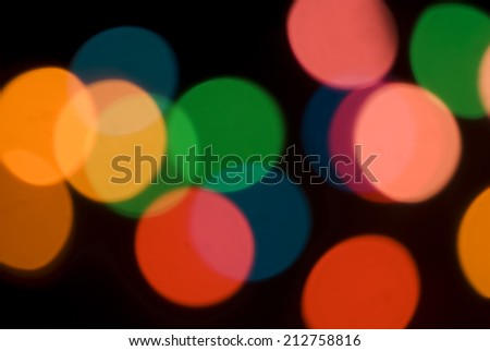 Bokeh of colorful party lights in red, orange and green for a festive background for a celebration or holiday - stock photo