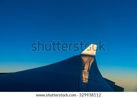 Bold blue sky reflecting of the wing of a commercial airliner as it banks to the left over a cloud bank.