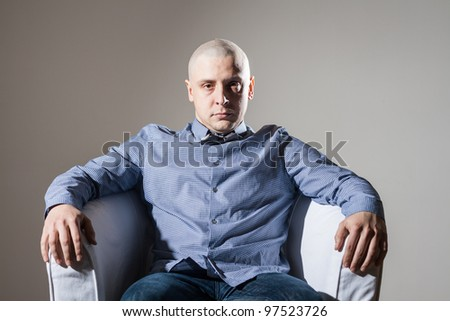 Bold man sit in a chair - stock photo