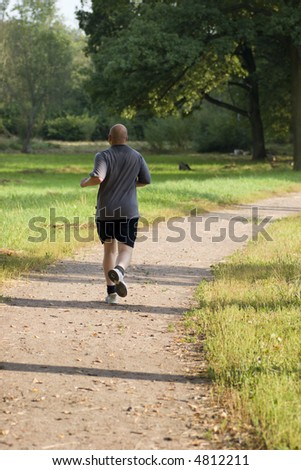 Bold muscular wet man jogging in the park in sunset lights - stock photo