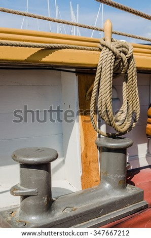 Bollard and rope of a sailing vessel, a close up - stock photo