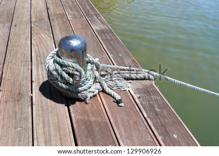 Bollard with white rope on wooden mooring in marina - stock photo