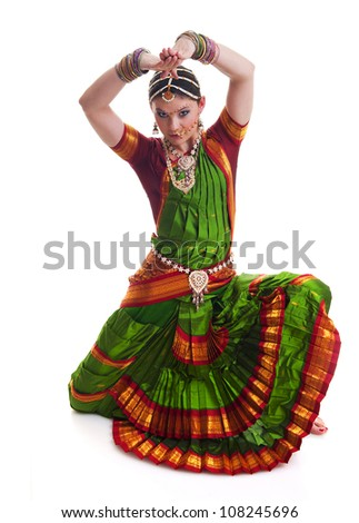 Bollywood dancer in green and orange folded dress posing as cobra - stock photo