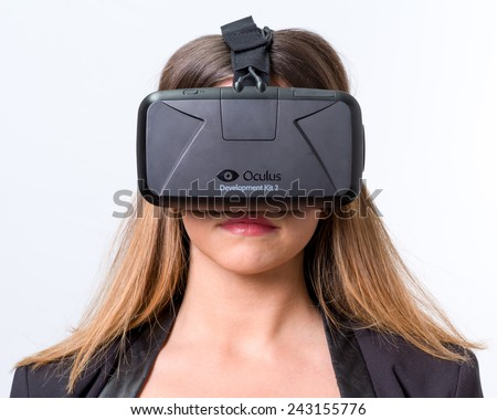 Bologna, ITALY - Jan 4, 2015: A woman wearing Oculus Rift. Rift is a wearable computer with an optical head-mounted display that is being developed by Oculus - stock photo