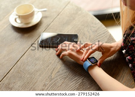 BOLOGNA, ITALY - MAY 17, 2015:  One girl wears the apple watch in a bar. - stock photo