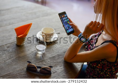 BOLOGNA, ITALY - MAY 17, 2015:  One girl wears the apple watch while using the iphone 6. - stock photo