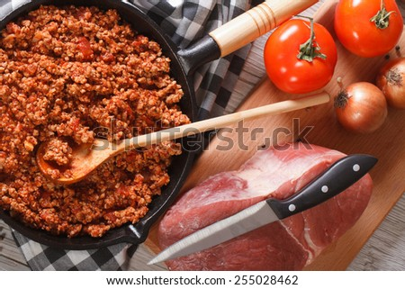 Bolognese sauce in a pan and ingredients on the table close-up. horizontal view from above - stock photo
