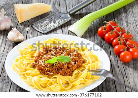 Bolognese sauce with italian pasta on a white plate, decorated with basil leaves, authentic recipe, wooden background with celery, garlic, cherry tomatoes and parmesan cheese, full focus, close-up - stock photo
