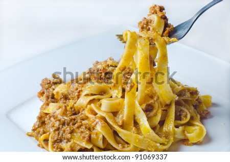 Bolognese sauce with parmesan, on tagliatelle pasta - stock photo