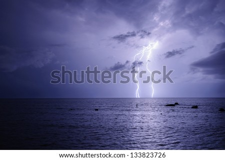 Bolt of lightning over night sea during a thunder-storm - stock photo