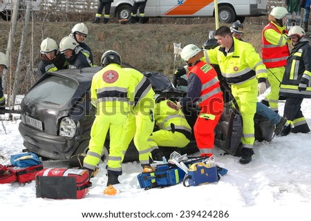 BOLZANO, ITALY - DECEMBER 23, 2014: : Dramatic scene of a huge crash with paramedics and fireman at work. Collision on snowy road in winter time after hitting a patch of ice on December 23, 2014 - stock photo