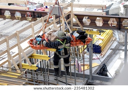 BOLZANO - ITALY, FEBRUARY 2, 2014: Firefighter rescue male worker out of an areal building site. Construction worker after hard accident crash on February 2, 2014 - stock photo