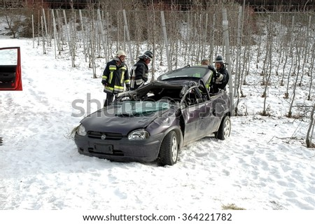 BOLZANO, ITALY - JANUARY 18, 2016: Car flipped over off the road. Firefighters on the accident scene caused by the high speed and the road made treacherous by ice and snow on Bolzano, Italy. - stock photo