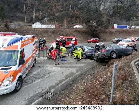 BOLZANO, ITALY - JANUARY 20, 2015: Paramedics and Firemen with ambulance car provide first aid to injured motorist after collision between two cars on iced road in winter time on January 20, 2015. - stock photo