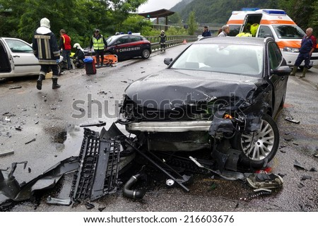 BOLZANO, ITALY - July 28, 2014: Huge car crash collision with two cars. Car accident on the road with injured motorist, intervention of paramedics and firefighters on July 28, 2014. - stock photo