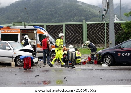 BOLZANO, ITALY - July 28, 2014: Paramedics Firefighters and police man working after a huge car crash collision. Car accident on the road with injured motorist on the road on July 28, 2014.
