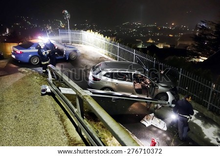 BOLZANO, ITALY - MAY 7, 2015: Crash collision in the night between car and barrier in the springtime. Car crashed into a gate of a house, with firefighters and police officer at work on May 7, 2015 - stock photo