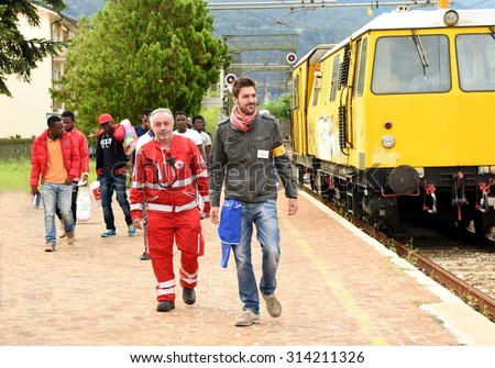 BOLZANO, ITALY - SEPTEMBER 5, 2015: Refugees fleeing the war leaving the train to arrive in a field for receiving first emergency, escorted by volunteers and medical doctors on September 5, 2015