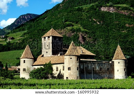 BOLZANO, ITALY:  The feudal Castello Mareccio with its enclosure wall, three round towers capped with conical roofs, and giant keep surrounded by Tyrolean vineyards - stock photo
