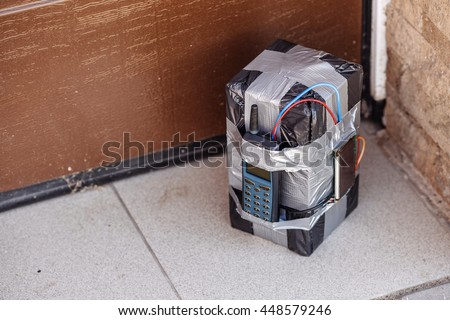 bomb with radio control and digital countdown timer near the garage door. terrorism and dangerous life concept - stock photo