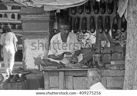 BOMBAY, INDIA - FEBRUARY 15, 1984: shoemaker at work in the biggest open air city market. The place is everyday populated by thousands of people.