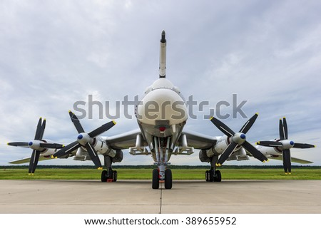 Bomber plane with propellers engines, military aircraft, air force, modern army aviation and aerospace industry, cloudy sky green grass and forest on background  - stock photo