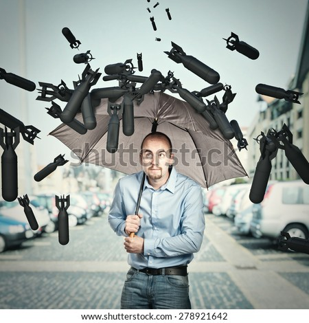 bombs and man try shield himself with umbrella - stock photo
