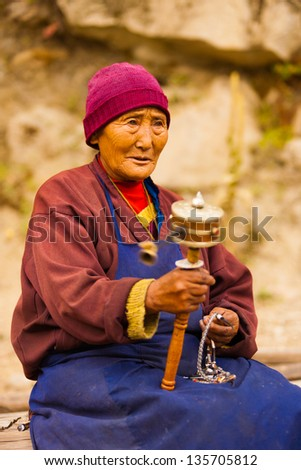 BOMI, CHINA - OCTOBER 15: An unidentified Tibetan pilgrim devoutly spins her prayer wheel, a buddhist ritual slowly lost on younger generations of Tibetans on October 15, 2007 in Bomi, China - stock photo