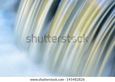 Bond falls cascade captured with motion blur and illuminated by reflected color from sunlit autumn trees, Michigan's Upper Peninsula.  - stock photo