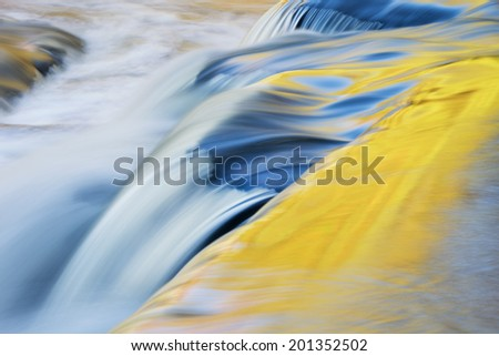 Bond Falls cascade captured with motion blur and illuminated by reflected color from sunlit autumn maples and blue sky overhead, Michigan's Upper Peninsula, USA  - stock photo