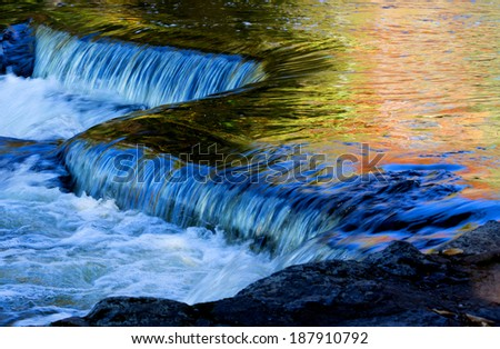 Bond Falls in Autumn. Surrounding autumn colors reflect in the clear waters of Bond Waterfalls on this wonderful sunny day in Michigan's Upper Peninsula. - stock photo