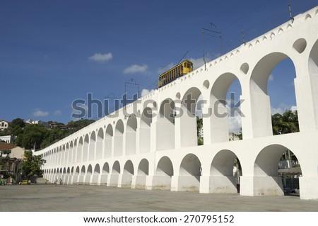 Bonde de Santa Teresa tram train drives along distinctive white arches of the landmark Arcos da Lapa in Centro of Rio de Janeiro Brazil - stock photo