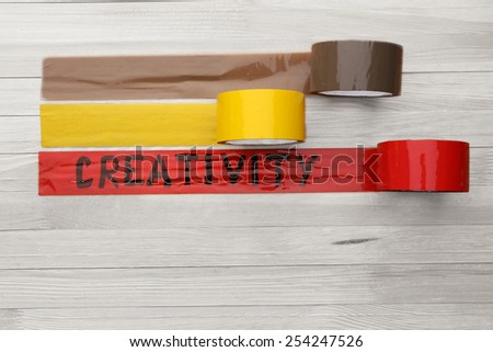Bonded tape on wooden planks background - stock photo