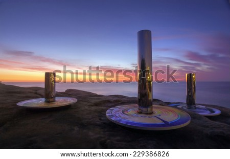 BONDI, AUSTRALIA - OCTOBER 23, 2014; Sculpture by the Sea .  Sculpture titled Coast Totem by Linda Matthews and Carterwilliamson , against a sunrise sky.  Made from chrome, steel, synthetic rubber - stock photo
