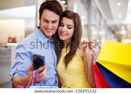 Bonding couple looking at mobile phone - stock photo